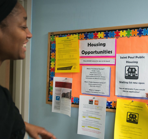 a woman looking at Housing Opportunities bulletin board