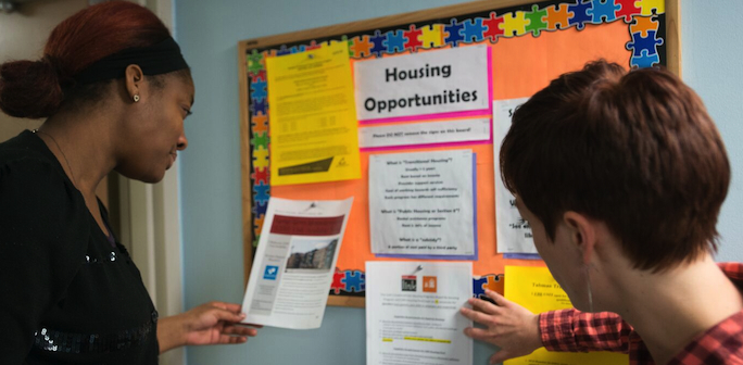2 women looking at Housing Opportunities bulletin board