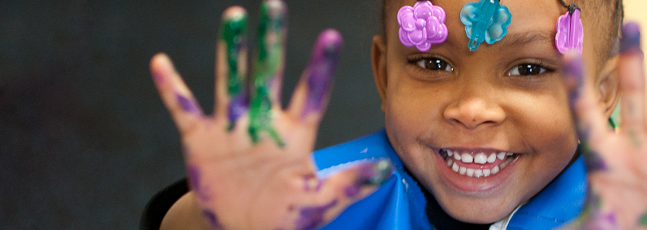 close-up: toddler smiling, showing us her open hands to covered in paint