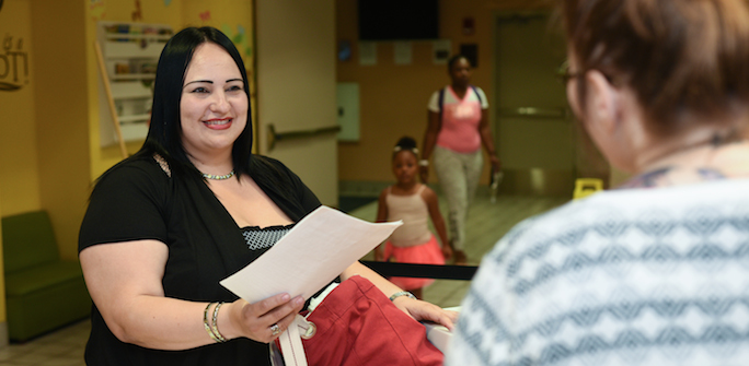 a woman handing paperwork to another