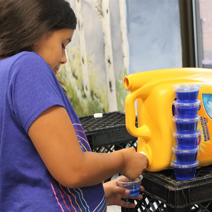 girl filling portion cup with laundry detergent, 6 more stacked nearby