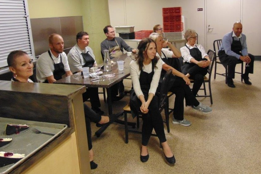 Current & former staff seated and listening to Volunteer Dinner program