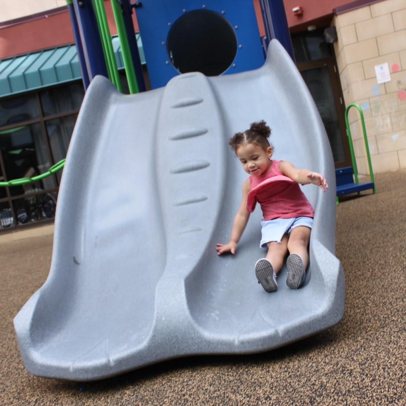 Girl sliding down the new slide
