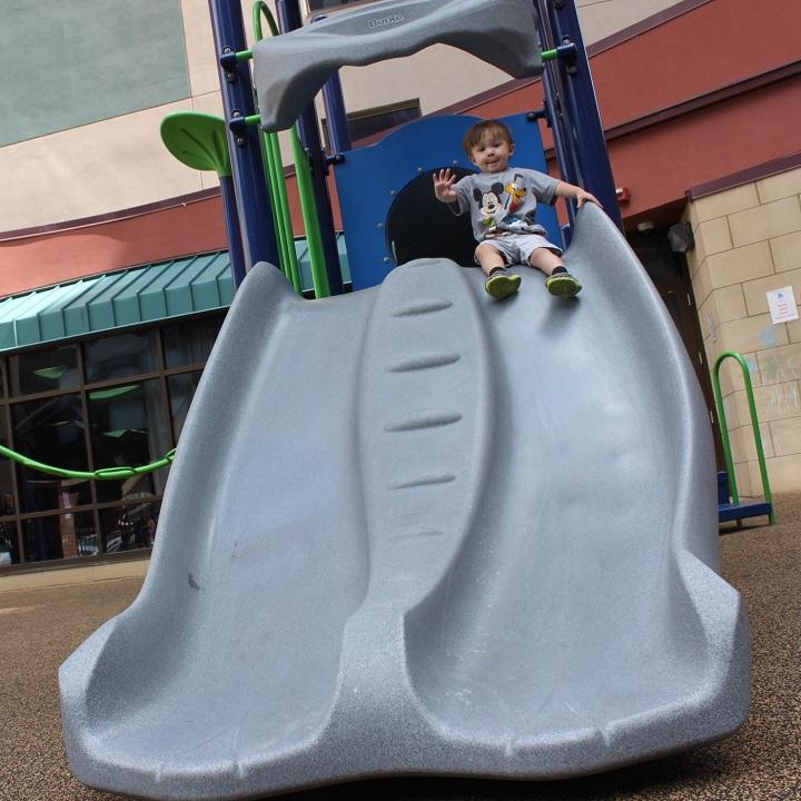 Boy sliding down the new slide