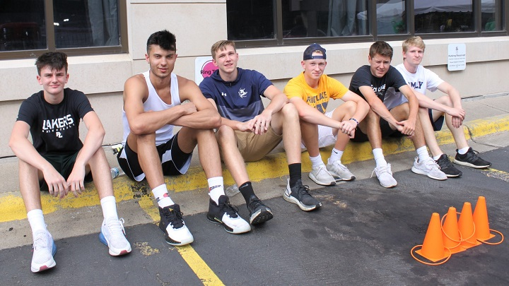 Prior Lake basketball team volunteers sitting on curb