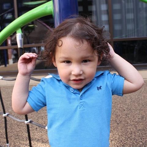 Close-up. Toddler boy in blue shirt.