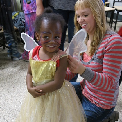 toddler being fitted with angel wings by volunteer