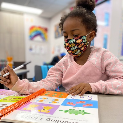 Close-up of young Black student in COVID mask and pink shirt holding a pen and looking at a colorful workbook.